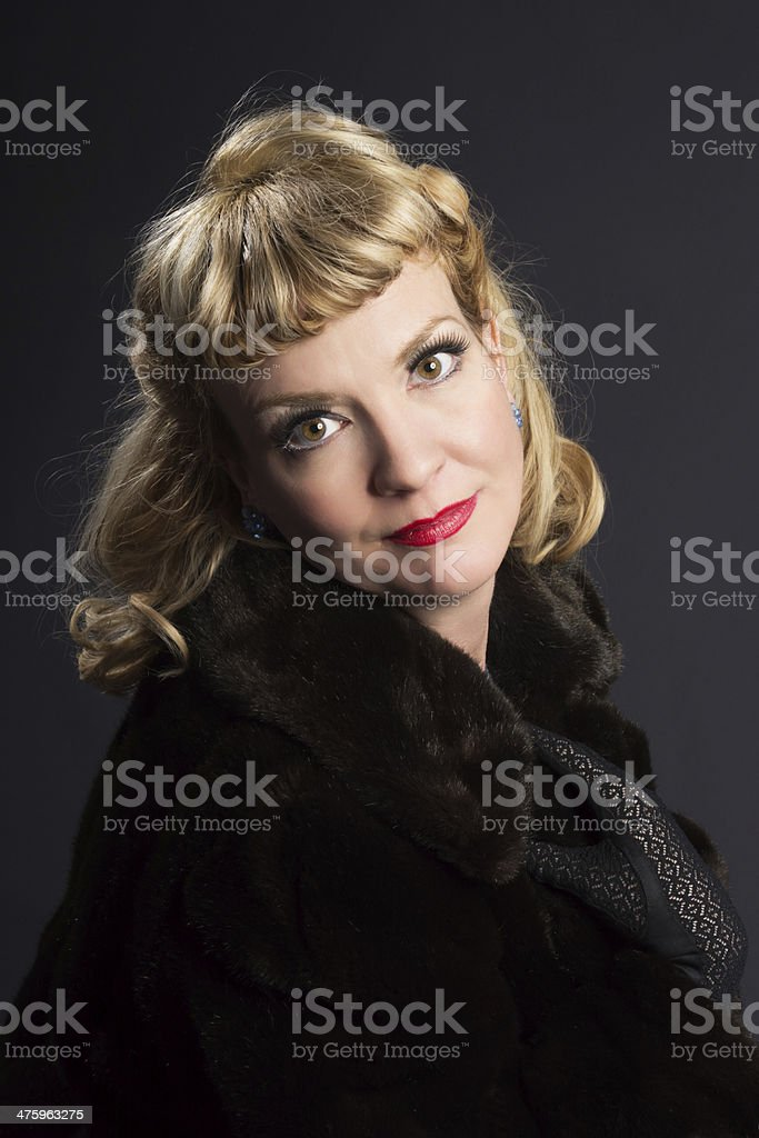 Glamourous blond mature woman in fur. royalty-free stock photo