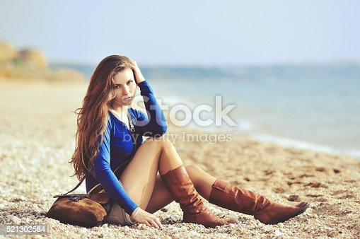 istock glamourous portrait of the young beautiful woman in leather boots 521302584