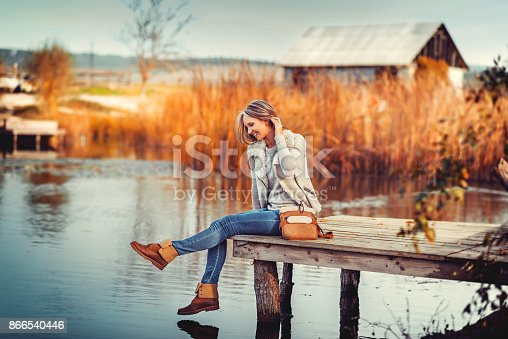 istock glamourous portrait of the young beautiful woman in leather boots 866540446