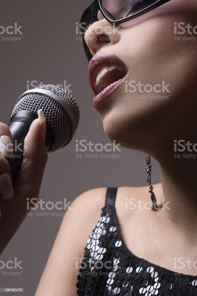 Glamourous Woman Singing Into Micophone royalty-free stock photo