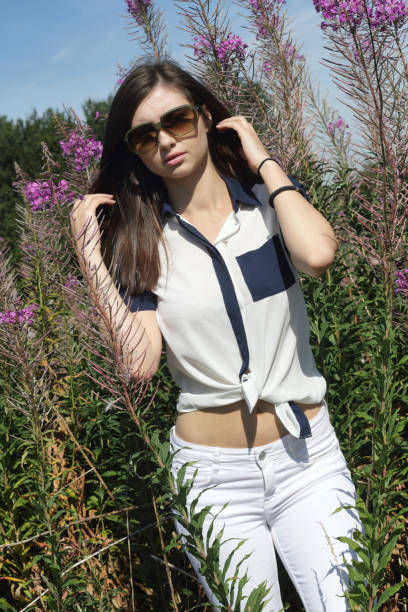 glamourous young bulgarian outdoor girl with fireweed wildflower - whiteway english outdoor girl stock photos and pictures