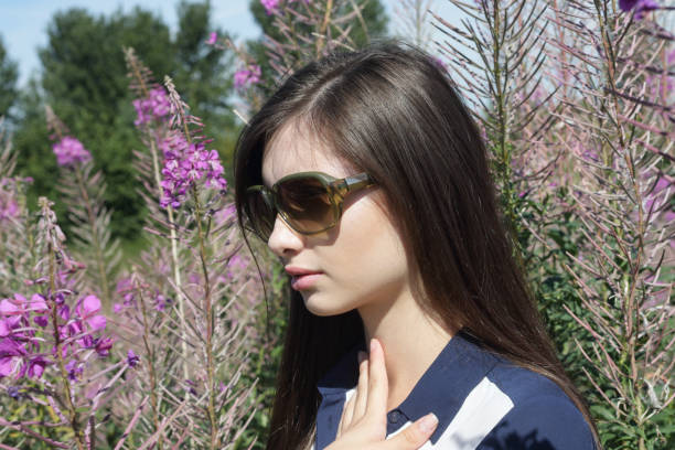 glamourous young bulgarian outdoor girl with fireweed wildflower - whiteway bulgarian outdoor girl stock photos and pictures