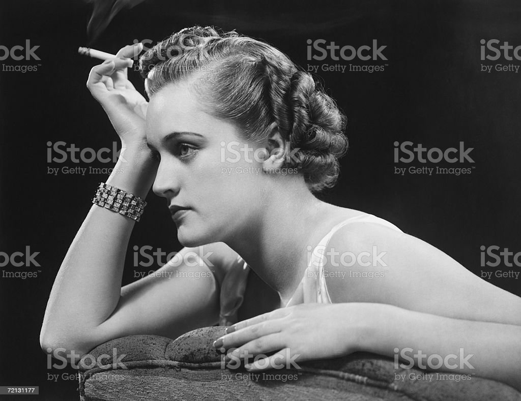 Glamourus woman sitting on sofa, holding cigarette (B&W) royalty-free stock photo