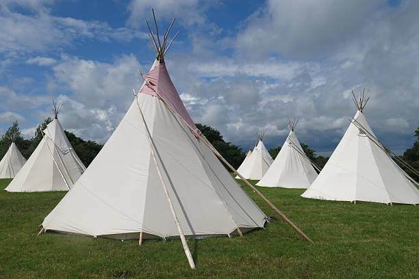 Glamping camping tipis tepees in a field on a sunny day stock photo
