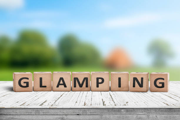 Glamping sign on wooden planks in the summer stock photo