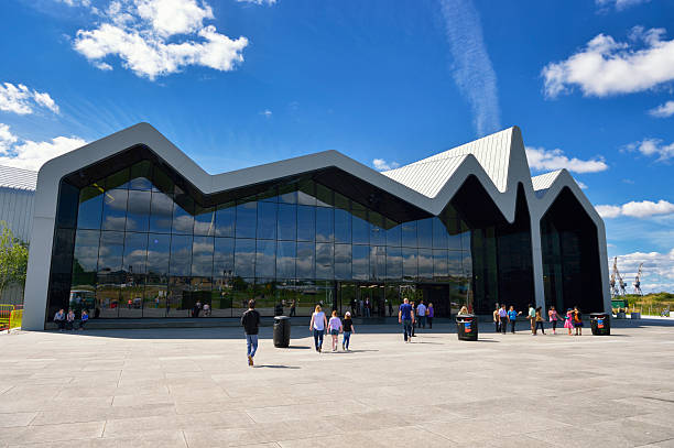 Glasgow riverside transport museum on a bright sunny day Glasgow, Scotland, UK - August 8, 2012: Members of the public outside the main entrance to The Riverside Museum which sits on the north bank of the River Clyde in Glasgow, in the distance the cranes of the Govan shipyards can also be seen. The Riverside Museum became the new home to the Glasgow Transport Museum after all of the exhibits were transferred from the old museum in the Kelvin Hall. johnfscott stock pictures, royalty-free photos & images