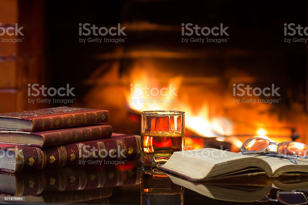 Glass alcoholic drink wine antique books in front warm fireplace. stock photo