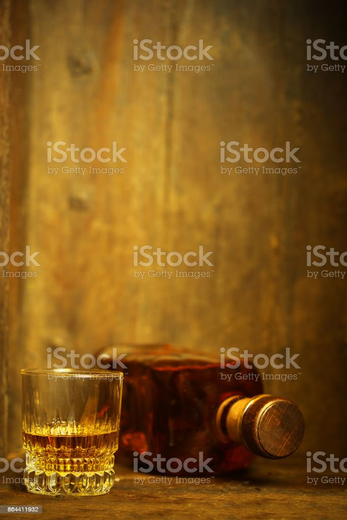 A glass and a bottle of whiskey on wooden background stock photo
