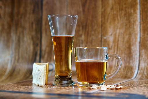 A glass and a mug of tasty beer stand on a brown background with cheese and nuts.