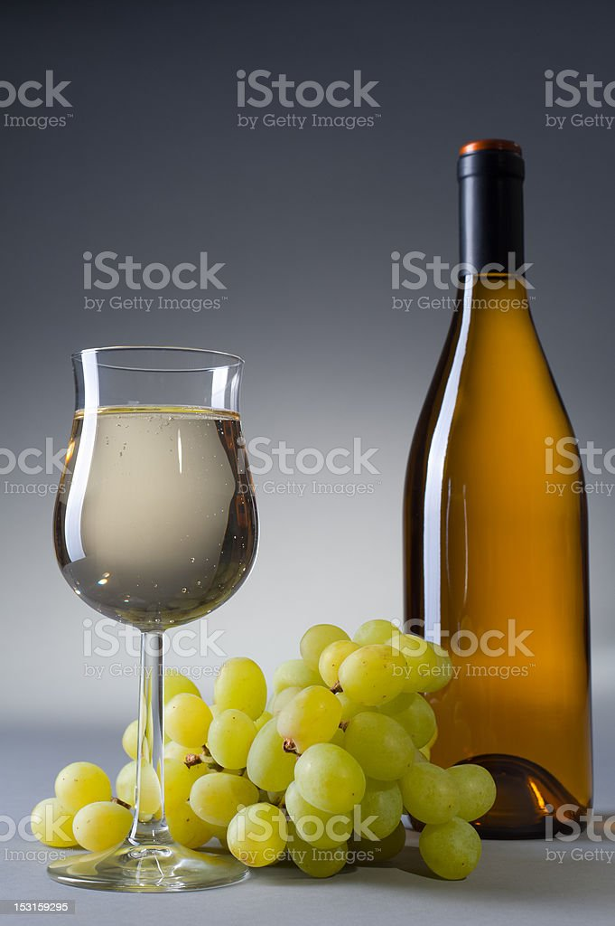 Glass and bottle full of white wine stock photo
