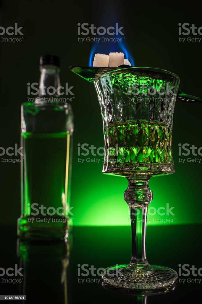 glass and bottle of absinthe with burning sugar on spoon on reflective surface and dark green background stock photo