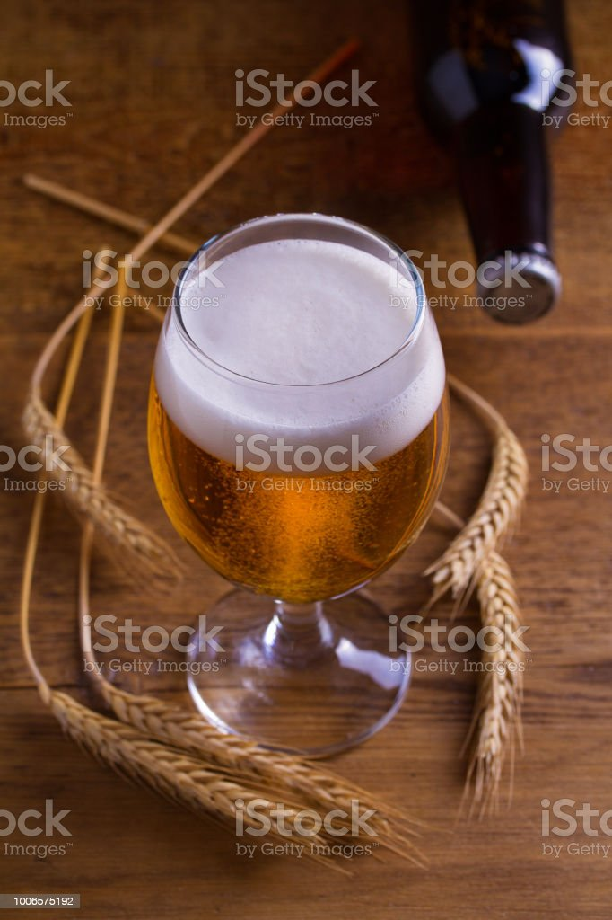 Glass and bottle of beer, ears of barley on wooden table stock photo