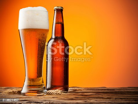 Glass with bottle of beer with blur orange background