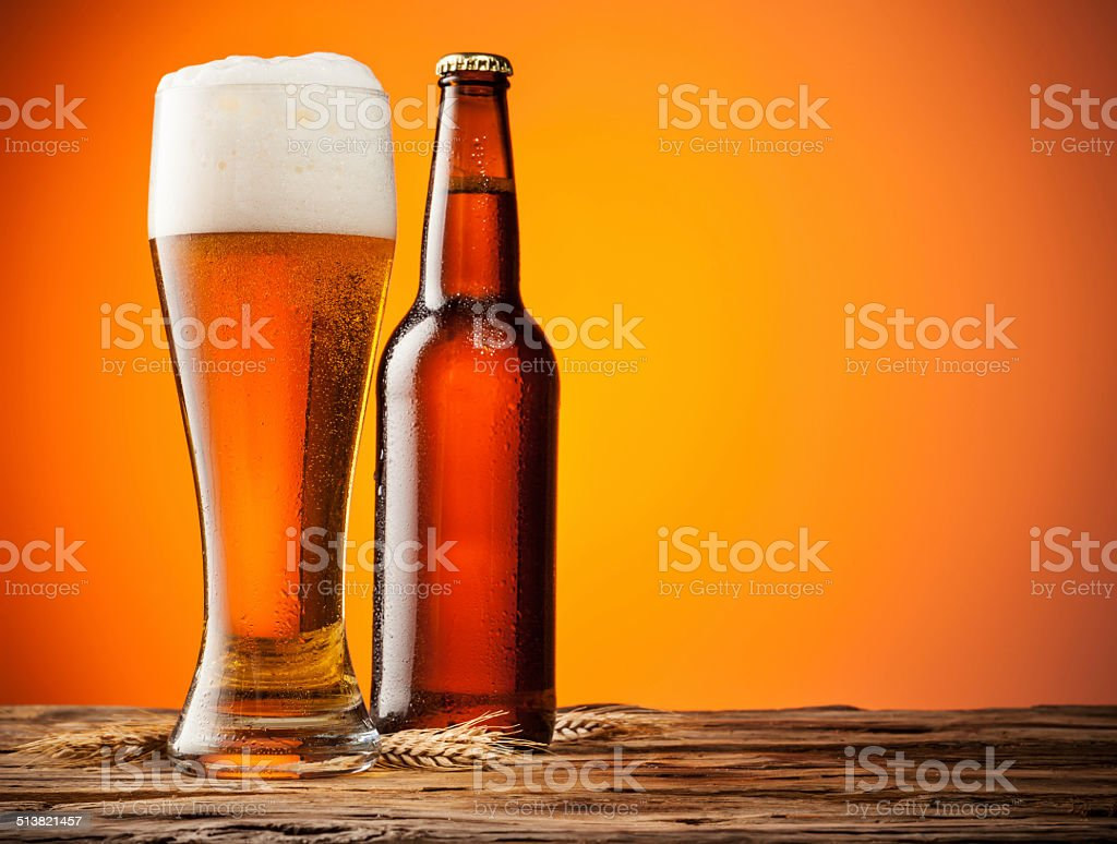 Glass and bottle of beer with orange background stock photo