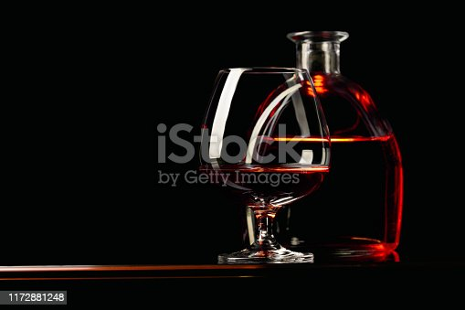 Glass and bottle of brandy on a black background. Copy space.