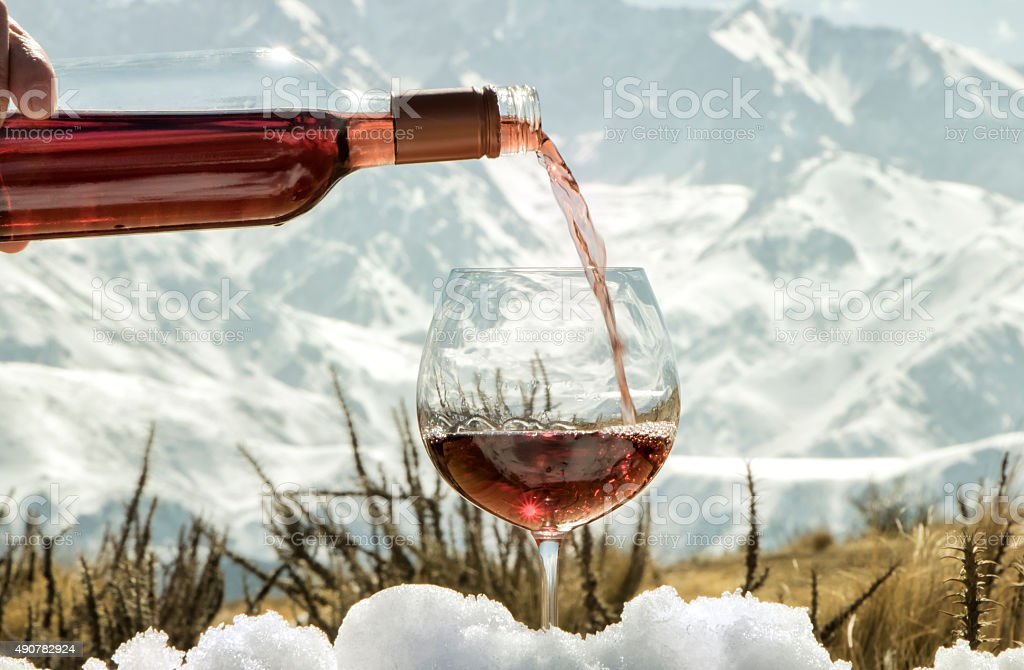 Glass and bottle of rosé wine on snow stock photo
