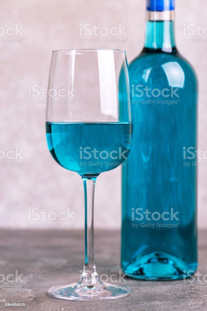 Glas und Flasche trendy blauen Wein. Spanischen blau Wein Chardonnay auf Beton dunkel – Foto