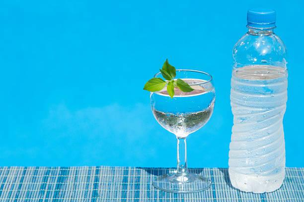 glas und flasche wasser auf bambus strohmatte - tropfenblatt tisch stock-fotos und bilder