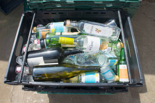 Glass and Bottle Recycling Marazion, Cornwall, UK - May 18, 2018: A tray holding glass and bottles ready for recycling in a small industrial yard. bottle bank stock pictures, royalty-free photos & images
