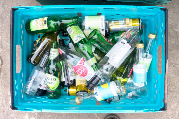 Glass and Bottle Recycling Marazion, Cornwall, UK - May 25, 2018: Overhead view of a tray holding glass and bottles ready for recycling in a small industrial yard. bottle bank stock pictures, royalty-free photos & images