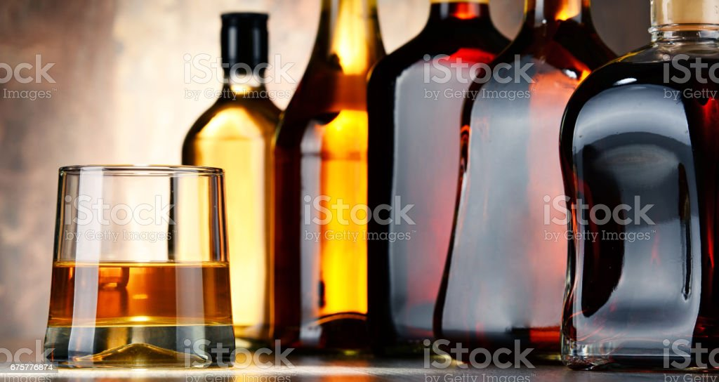 Glass and bottles of assorted alcoholic beverages stock photo