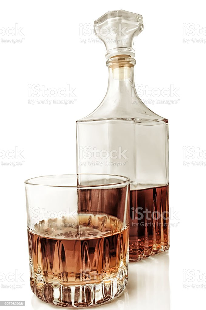 Glass and decanter with alcohol on a white background with reflection. stock photo