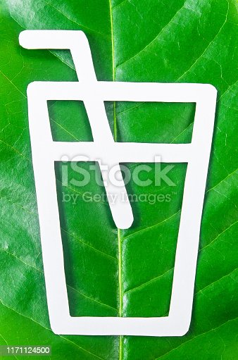 glass ans straw made from paper cut out on leaf green tree. Biodegradable package concept.