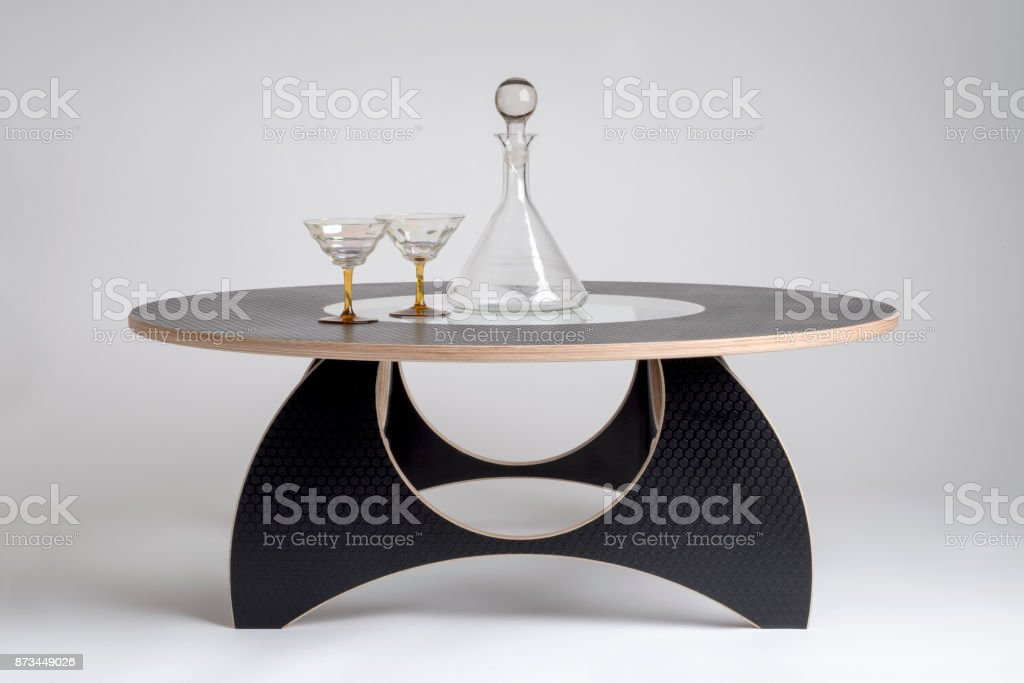 Glass Aperitif and Flask on Black Designer Round Table stock photo