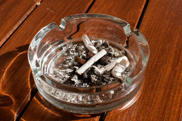 Glass ashtray with butts Glass ashtray with cigarette butts and ashes on wooden board deleterious stock pictures, royalty-free photos & images