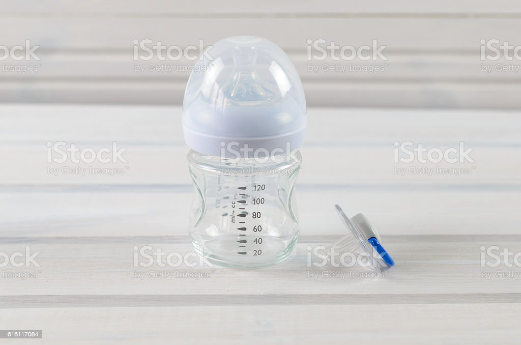 Glass baby bottle and baby pacifier on white wooden background stock photo
