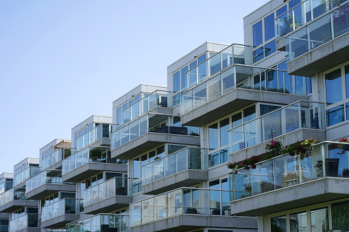 Closeup of an apartment building with balconies from the village. Background of windows and balconies of a multi-storey glass building.