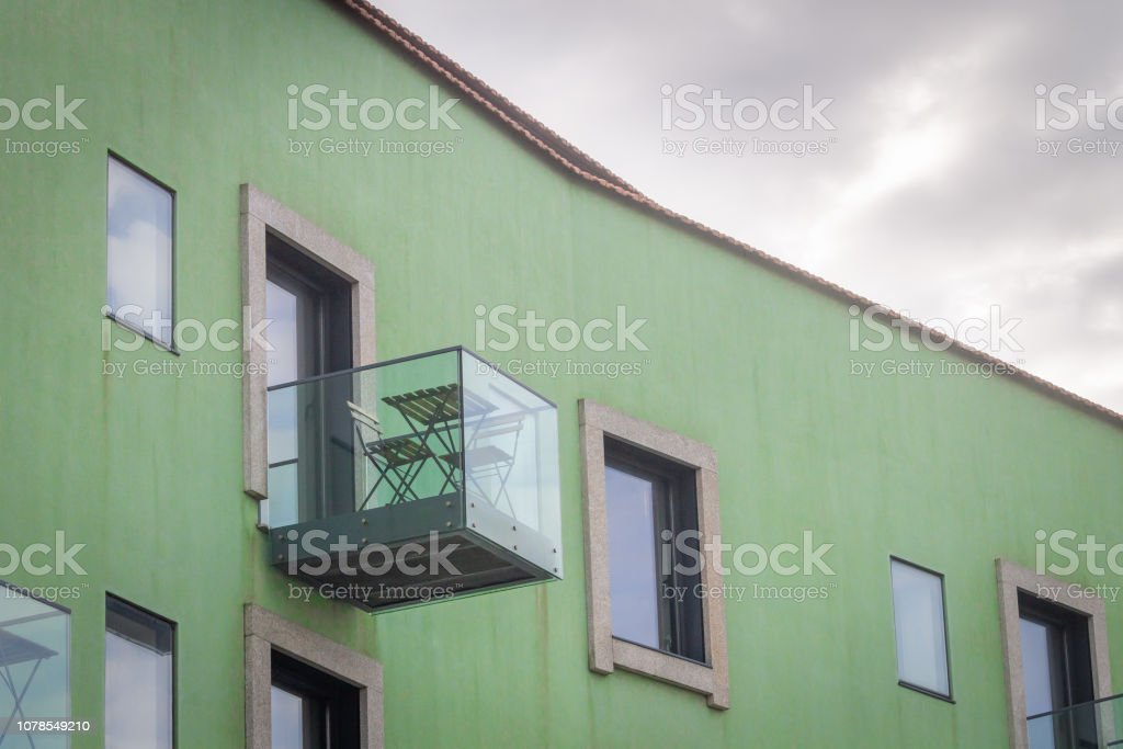 Side view of a glass balcony with a wooden table and chairs, on a...