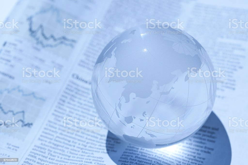 A glass ball containing a map of Asia, upon newspaper stock photo