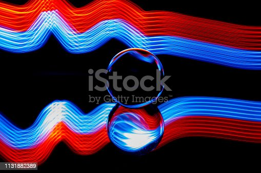 istock Glass ball light painting - blue  and red stripes 1131882389