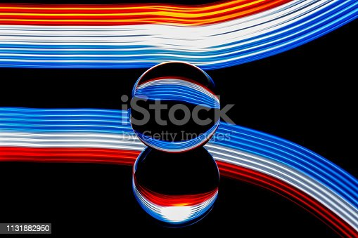 istock Glass ball light painting - blue  and red stripes 1131882950