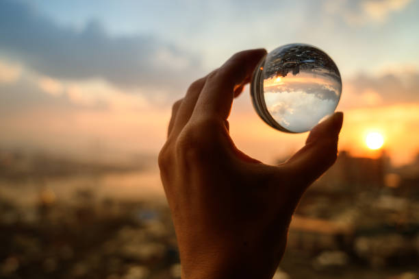 Glass ball which reflects sunset sky over city. stock photo