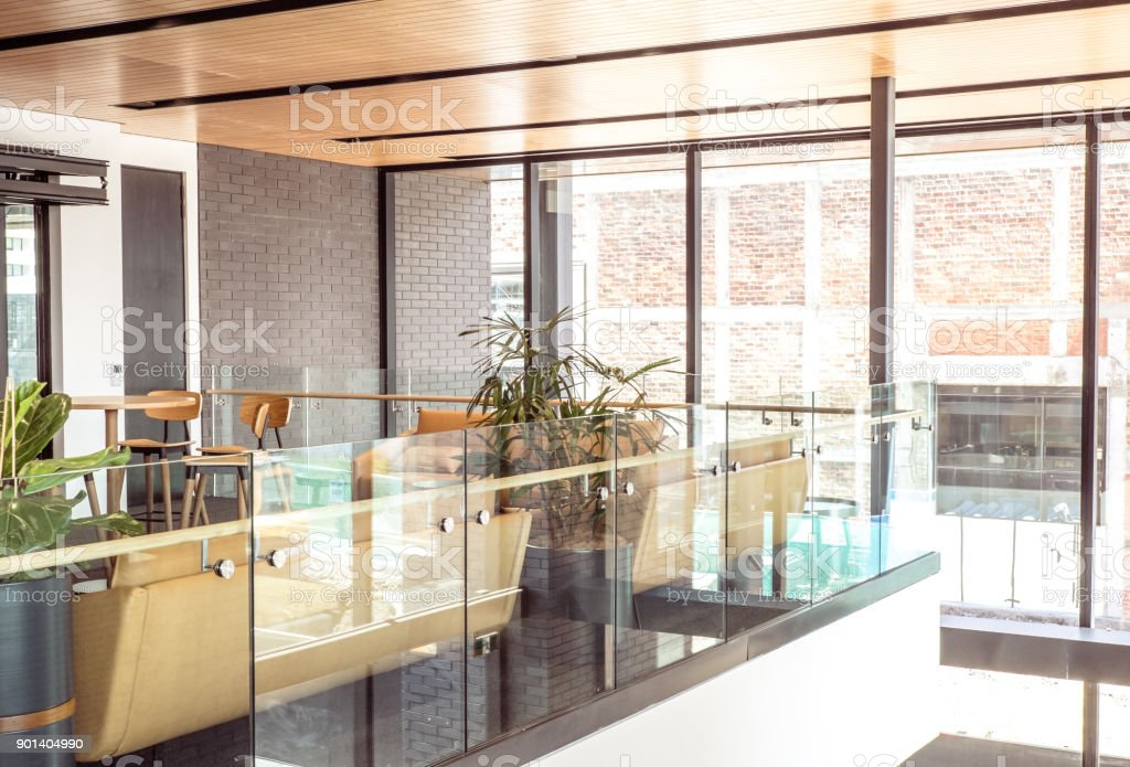 Glass balustrade in a modern open plan office building - airy bright interior design with large windows in background, plus meeting area with stools, couch and sofa stock photo