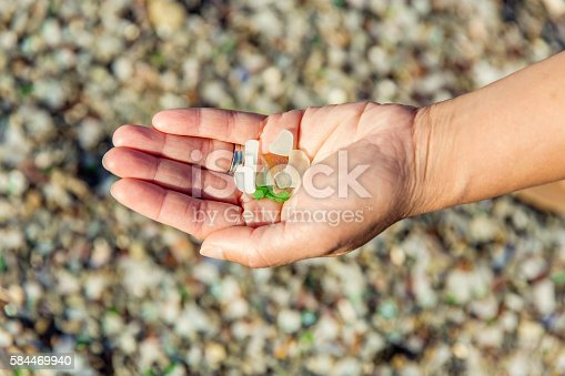 Stock photo of a hand holding a handfull of glass washed up on a beach.