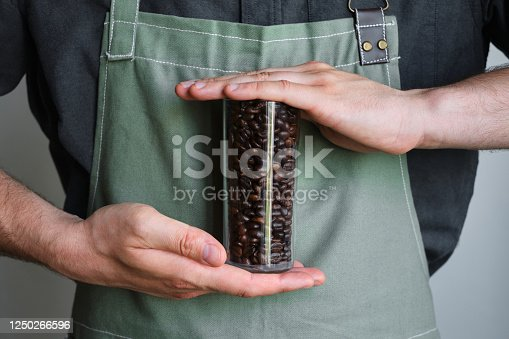 istock A glass beaker with coffee beans in the hands of a barista. Ready to brew roasted coffee. A man in a culinary apron. Fresh organic coffee. Disposable paper cup. Making coffee, professional service 1250266596