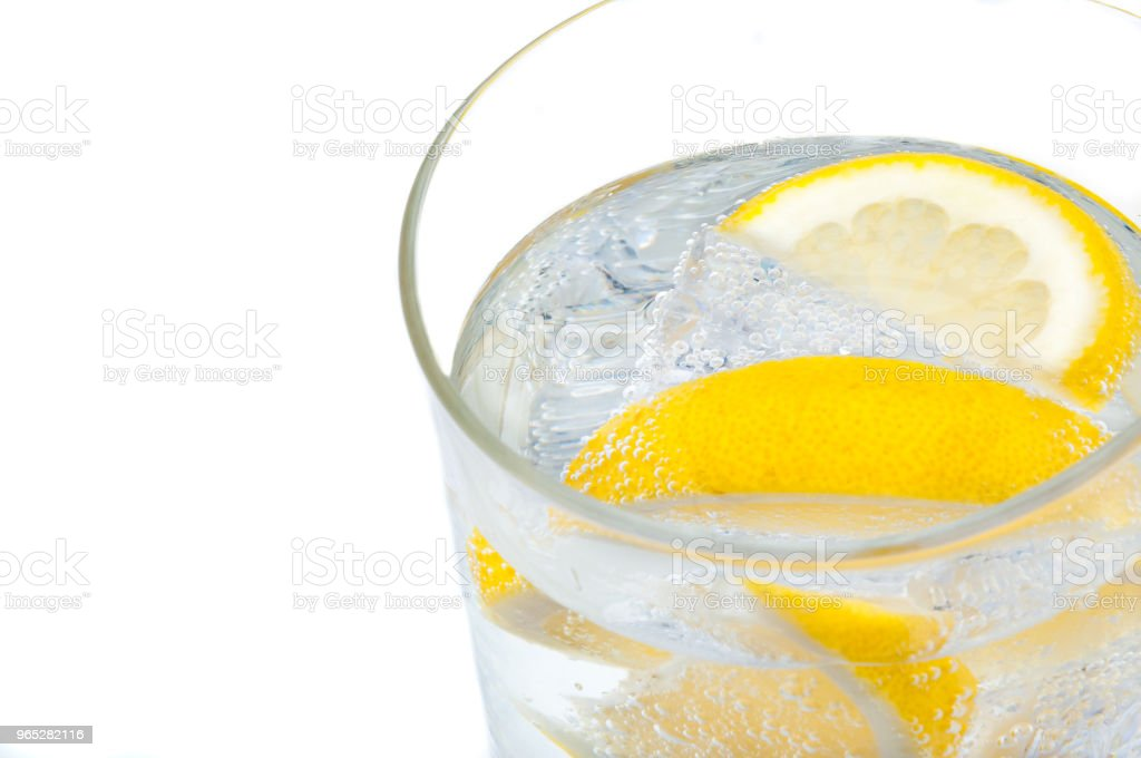 A glass beaker with crystal clear water, lemon and ice cubes. royalty-free stock photo