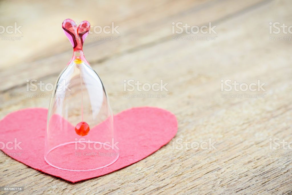 Glass bell and a red mulberry paper heart on a wooden table. stock photo