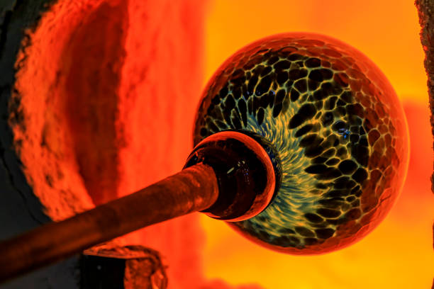 Glass blower working on a bubble of melted glass on a rod by heating it up in a kiln at a glass maker's workshop stock photo