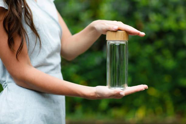 glass bootle in woman hands. - riutilizzabile foto e immagini stock