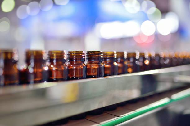 glas flasche füllen - braunglasflaschen stock-fotos und bilder