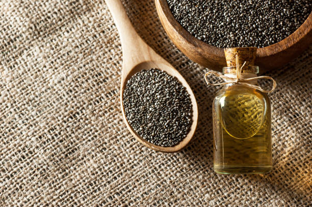 Glass bottle of chia oil and Chia seeds ( Salvia Hispanica ) in wooden spoon and bowl on burlap sack backdrop stock photo