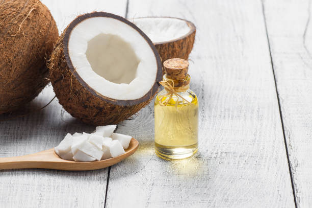 Glass bottle of coconut oil with fresh coconut fruit on rustic background, alternative theraphy medicine concept, Cocos nucifera Glass bottle of coconut oil with fresh coconut fruit on wooden rustic background, alternative theraphy medicine concept, Cocos nucifera coconut oil stock pictures, royalty-free photos & images