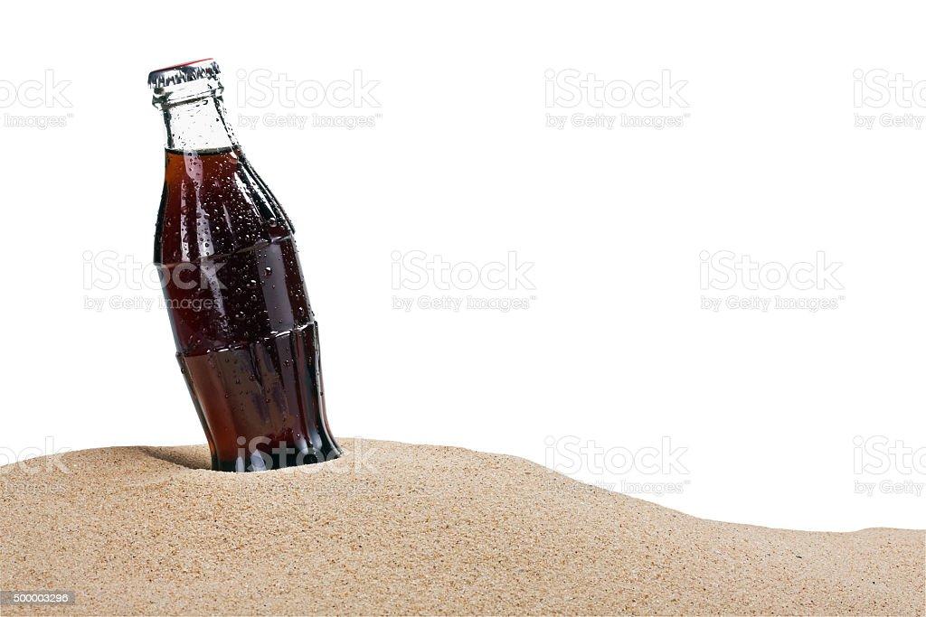El frasco de vidrio de cola en la arena - foto de stock