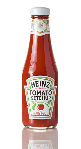 glass bottle of heinz tomato ketchup on a white background - heinz stock photos and pictures