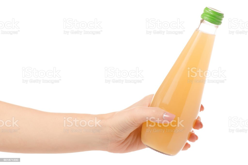 Glass bottle of juice in a hand stock photo