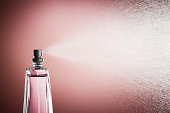 Glass bottle of perfume spraying mist against pink background